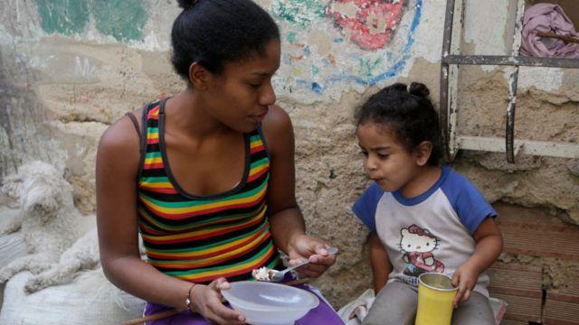Una mujer y una niña fuera de una casa