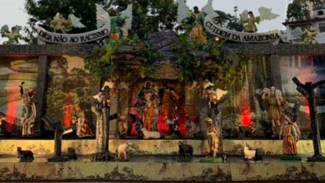 """Presépio criado pelo pároco Wanderson Guedes traz uma Sagrada Família negra e anjos segurando uma faixa com os dizeres: """"Digam não ao racismo""""."""