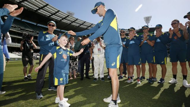 Australian cricket captain Tim Paine hands Archie Schiller a baggy green cap amid applause from teammates