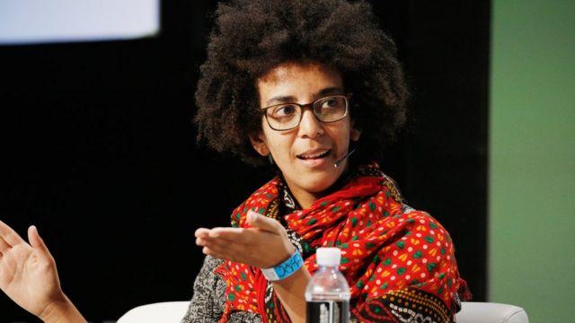Gebru, uma mulher jovem e negra de óculos, fala no palco de um evento em 2008