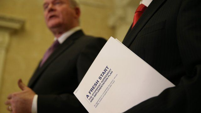 First Minister Peter Robinson holds a copy of the agreement as he speaks alongside Deputy First Minister Martin McGuinness