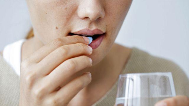 Mulher coloca pílula na boca