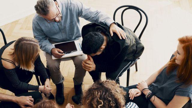 Hombre llorando en una reunión