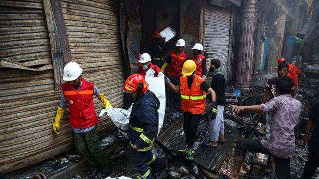 อาสาสมัครกำลังกู้ศพจากโกดังที่ถูกไฟไหม้ในกรุงธากา