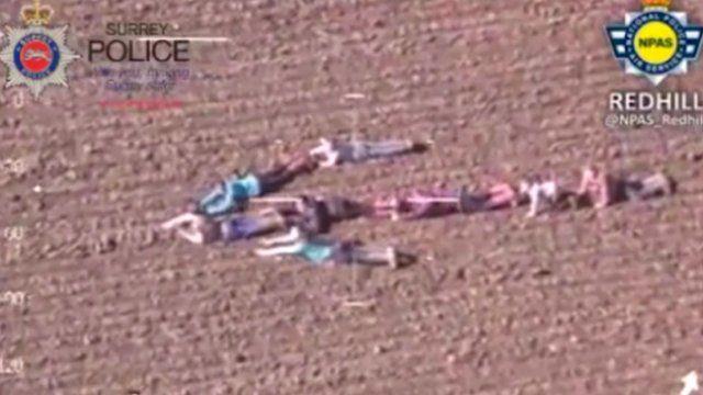 Children lying down in field, forming an arrow shape