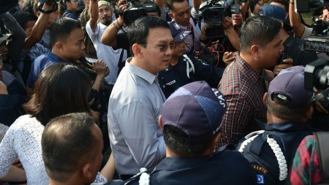 Incumbent Jakarta governor Basuki Tjahaja Purnama (C) is surrounded by journalists after voting at a polling station during the final-round of the Jakarta governor election in Jakarta on April 19, 2017