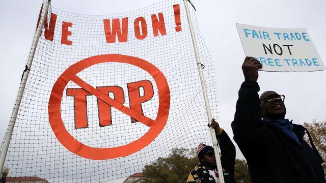 Personas con carteles en contra del TPP.