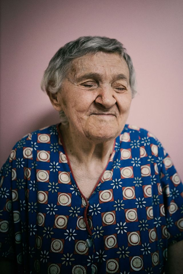 A blind woman poses for a portrait against a pink wall