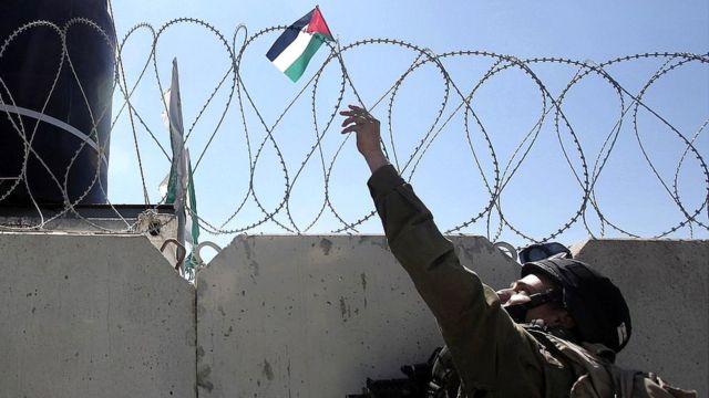 Soldado israelí retira una bandera palestina del muro en Cisjordania