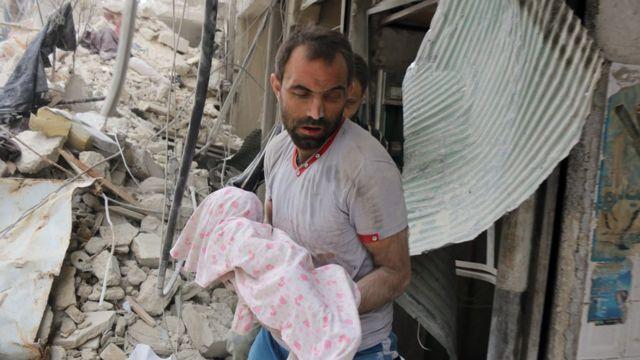 Un hombre carga un bebé cubierto tras un ataque en Alepo, Siria