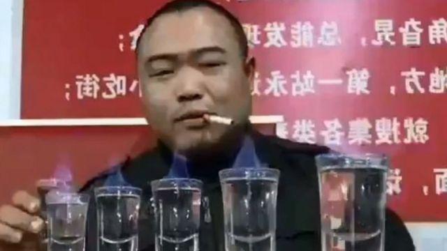 Liu Shichao fumando ao lado de copos com bebida