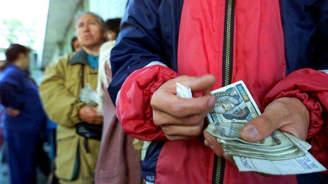 Ecuatorianos cambiando sucres por dólares en 2000.