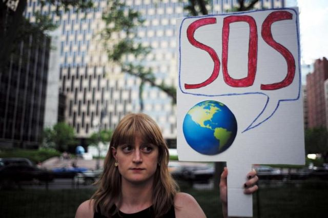 Una mujer sostiene un cartel con el planeta tierra diciendo SOS.