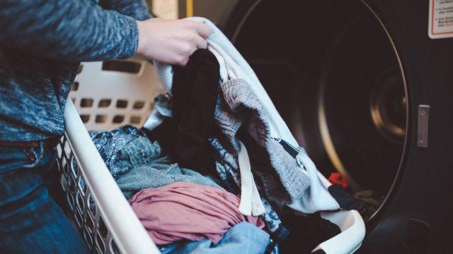 Una persona pone ropa en la lavadora