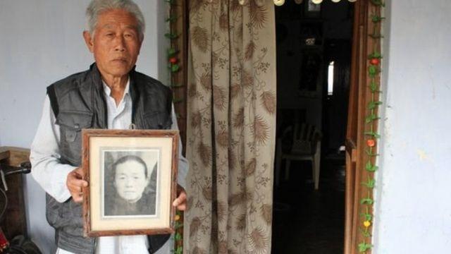 Ông Vương cầm ảnh mẹ, người qua đời năm 2006 mà không được gặp lại con.