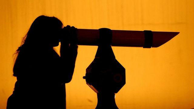 Mujer mirando por un telescopio