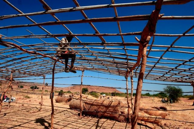 لاجئ من إقليم تيغراي في إثيوبيا يشرع في بناء منزل له بعد فراره من القتال الدائر في الإقليم ولجوئه إلى السودان.