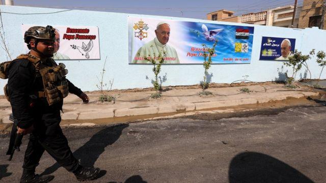 Член силовых структур Ирака на фоне плакатов к приезду папы Франциска
