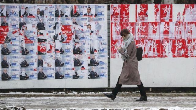 Žena prolazi pored zida na kojem se vide posteri suparničkih političkih kandidata u Moldaviji