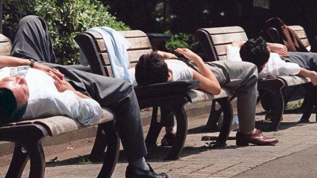 Hombres japoneses durmiendo una siesta en las sillas de un parque