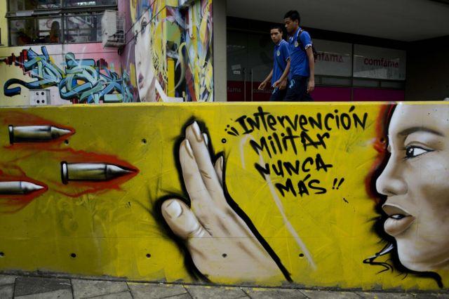 """Mural amarillo en el que se puede leer """"Intervención Militar Nunca Más""""."""