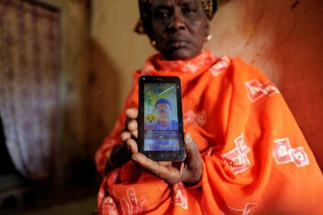 أميناتا غويي في السنغال تنظر إلى صورة ابنها محمد البالغ من العمر 24 عاماً الذي لقي مصرعه في البحر أثناء محاولته الوصول إلى جزر الكناري التابعة لإسبانيا