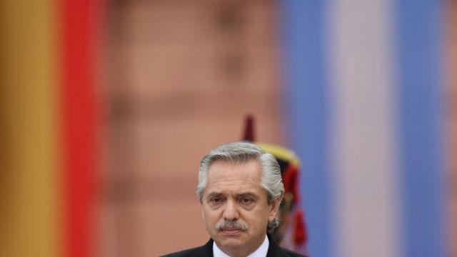 Fernández com olhar sério em frente a bandeiras e soldado de cavalaria