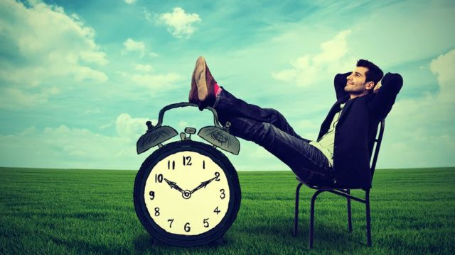 Hombre descansando con los pies sobre un reloj.