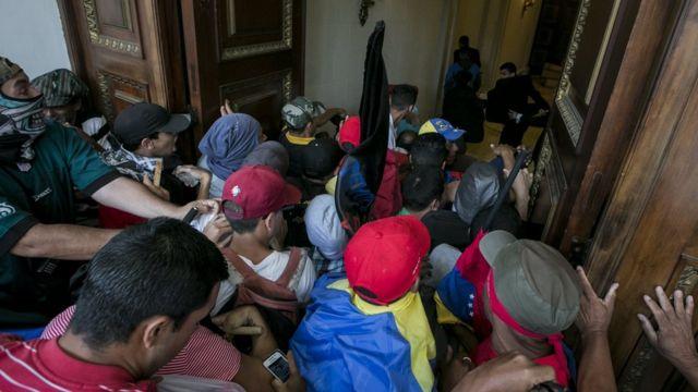 Un grupo de personas empujan una puerta para entrar al Palacio Legislativo.