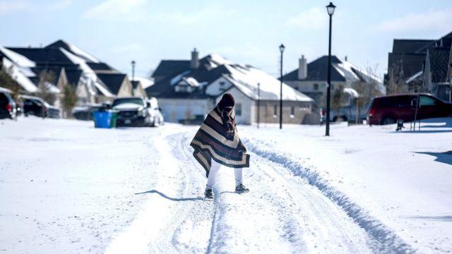 رجل يسير إلى منزل صديقه في حي بدون كهرباء بينما يغطي الثلج حي بلاك هوك في بفلوغرفيل، تكساس، 15 فبراير/شباط 2021