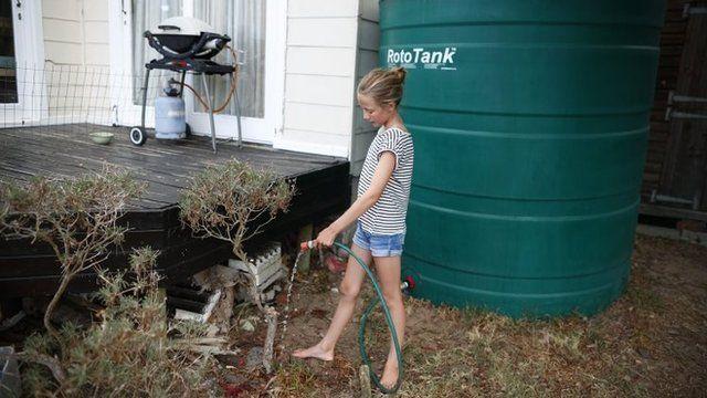 Una joven riega las plantas con agua de lluvia proveniente de un tanque en Ciudad del Cabo.