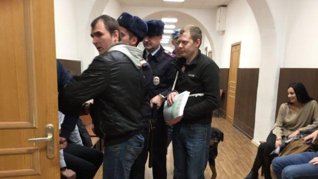 Конвой заводит двоих мужчин в судебный зал