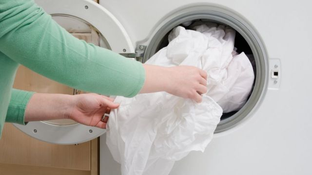 Las manos de una mujer llenando la lavadora con ropa de cama