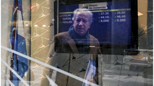 أرجنتيني يطالع سعر صرف البيزو مقابل عملات أجنبية في مكتب للصرافة