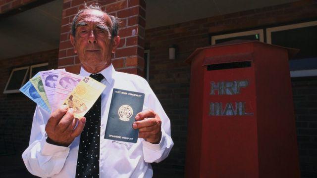 El autoproclamado Príncipe Leonardo muestra el pasaporte y la moneda del principado.