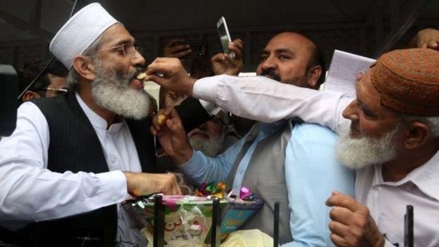 ซิราช อุล ฮัก (ซ้าย) หัวหน้ากลุ่มจามาอัต-อี-อิสลามี มอบขนมให้แก่ผู้สนับสนุนฝ่ายค้าน