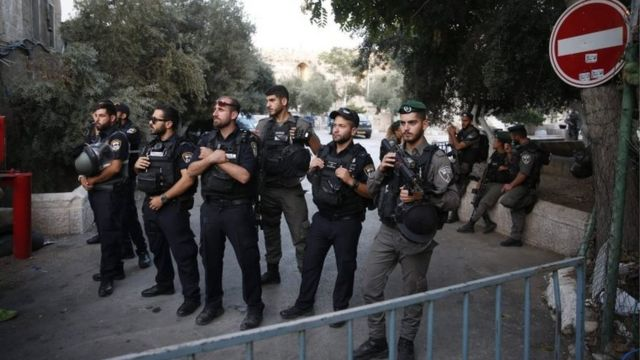 Israeli security forces hold a position as Palestinian Muslim worshippers gather to pray outside Jerusalem's Old City on 25 July 2017