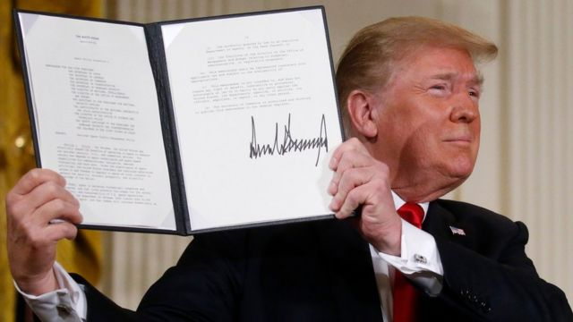 US President Donald Trump displays his signature after signing a national space policy directive during a meeting of the National Space Council