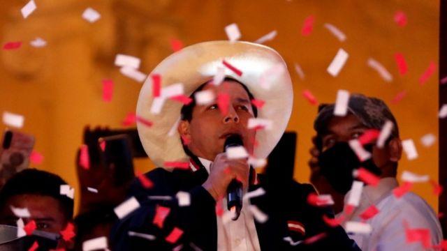 De chapéu, Castillo fala no microfone à noite, com papel picado voando na frente