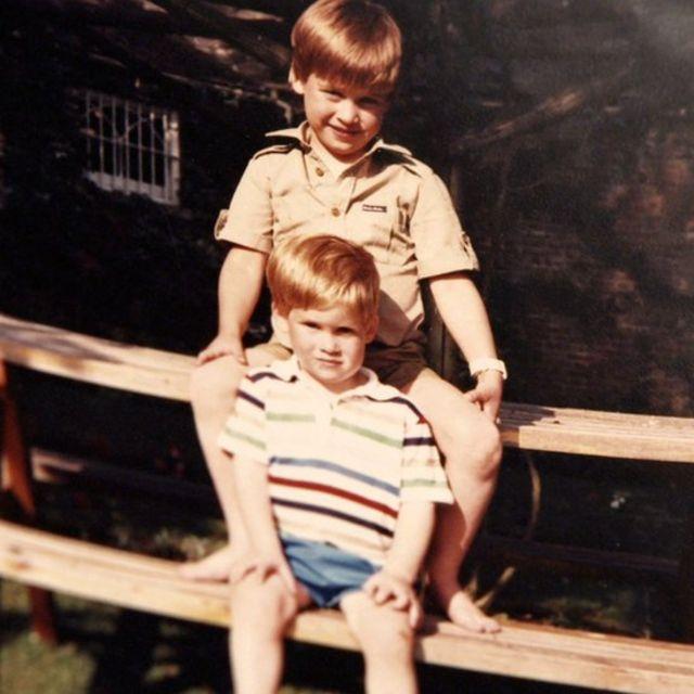 Príncipe William e príncipe Harry em um banco de piquenique