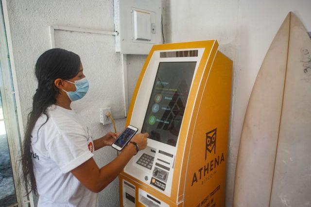Una mujer retira efectivo de una ATM de bitcoins.