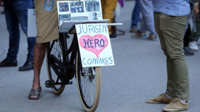 Un ciclista monta una bicicleta con una pancarta en apoyo al soldado belga de extrema derecha Jürgen Conings el 29 de mayo