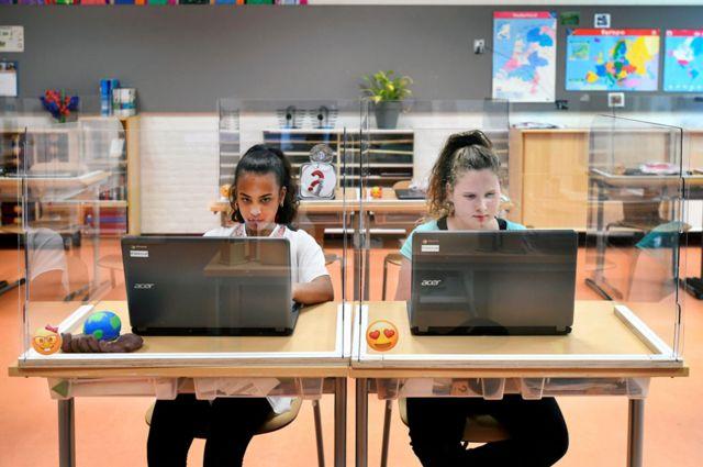 Dos alumnas en una escuela en Países Bajos, con plexiglass alrededor de sus pupitres.
