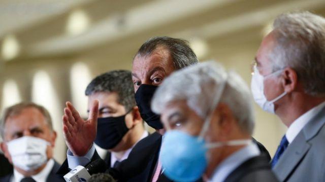 Lado a lado, senadores aparecem de máscara, um deles, Omar Aziz, falando e gesticulando