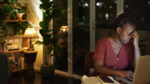 Nerwowo wyglądająca młoda kobieta pracująca przy laptopie w domu w nocy.