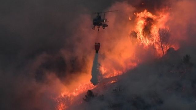A helicopter drops water on the wildfire near Vitrolles