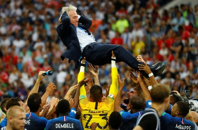 France coach Didier Deschamps is thrown into the air by his players as they celebrate after winning the World Cup, 15 July 2018