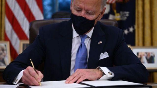 Biden firmando una orden ejecutiva