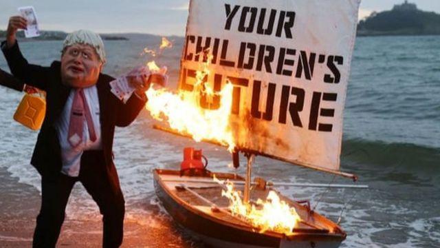 Okyanus İsyani adlı iklim eylem grubu Cornwall'da yapılacak G7 zirvesi öncesinde üzerinde 'Çocuklarınızın geleceği' yazılı bir tekne maketini ateşe verdi