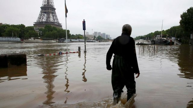 A man walks on a flooded road near his houseboat moored near the Eiffel towel during flooding on the banks of the Seine River in Paris, France